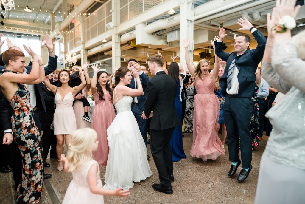 A bride and groom and people around them dancing